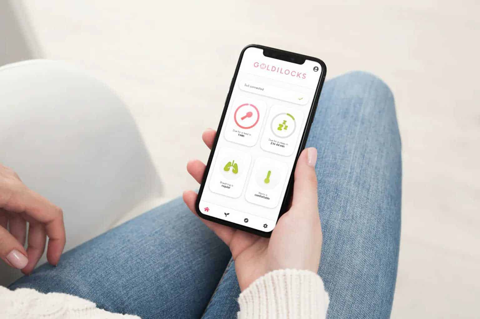 Why was the Goldilocks Suit Baby Monitor Made? A young mother using the Goldilocks Suit App for iOS and Android mobile phones to monitor their baby